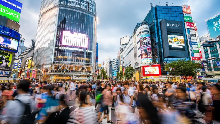 Blurred motion of people walking at the busy Shibuya Crossing.