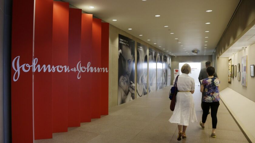 People walk along a corridor at the headquarters of Johnson & Johnson in New Brunswick, N.J., in 2013.
