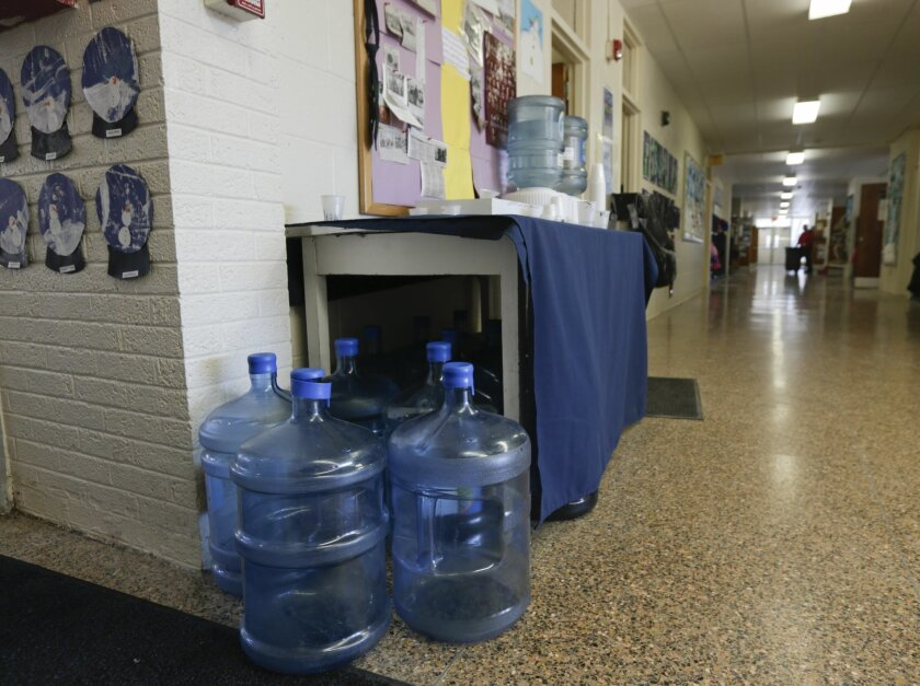 FILE - In this Jan. 21, 2016 file photo, bottles of drinking water are seen in a hallway at St. Mary's Academy in Hoosick Falls, N.Y. New York regulators say Saint-Gobain Performance Plastics and Honeywell International are required to pay for the investigation and cleanup of a toxic chemical in an