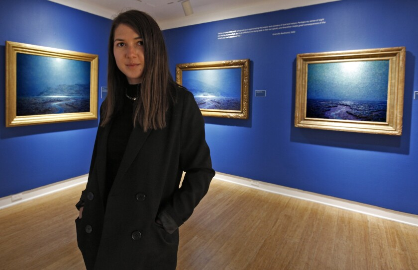 Laguna Art Museum teaching artist Ina Rosca poses in front of night scenes by painter Granville Redmond.
