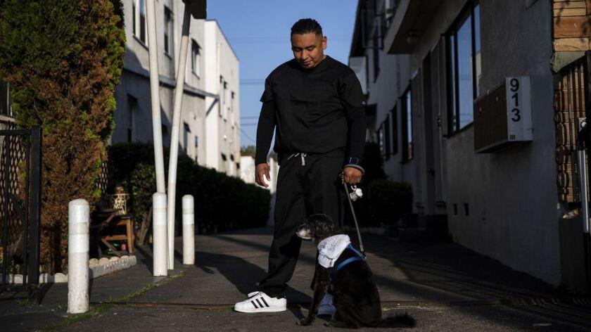 Maynor García con el perro de su hermano fallecido, Gabriel Dirzo, quien según sospechan los funcionarios médicos del condado de Los Ángeles murió después de inhalar cocaína mezclada con fentanilo (Kent Nishimura / Los Angeles Times).
