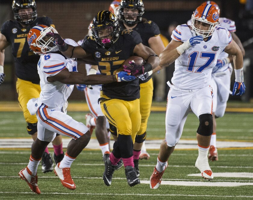 FILE - In this Oct. 10, 2015, file photo, Missouri running back Russell Hansbrough, center, fights his way past Florida's Nick Washington, left, and Jordan Sherit, right, during an NCAA college football game in Columbia, Mo. Some Missouri football players announced Saturday night, Nov. 7, 2015, on
