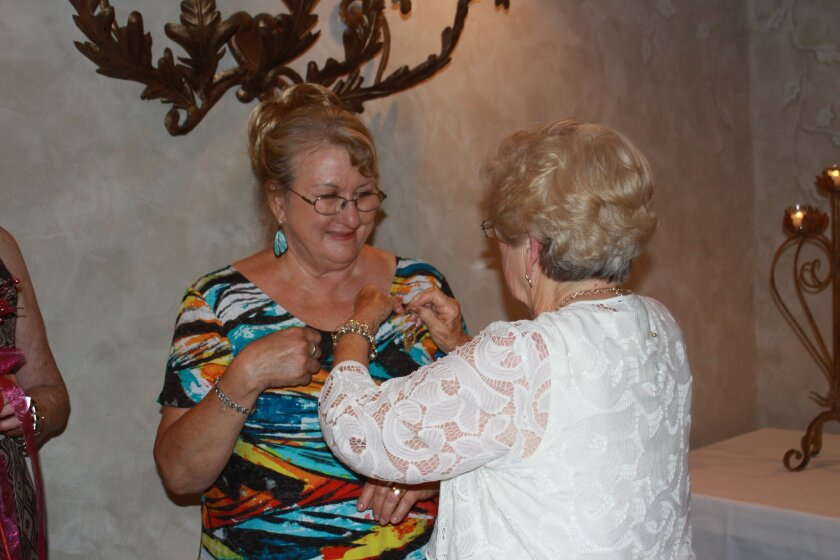 Incoming president Bonnie Mendenhall receives her President's Pin at the installation dinner.