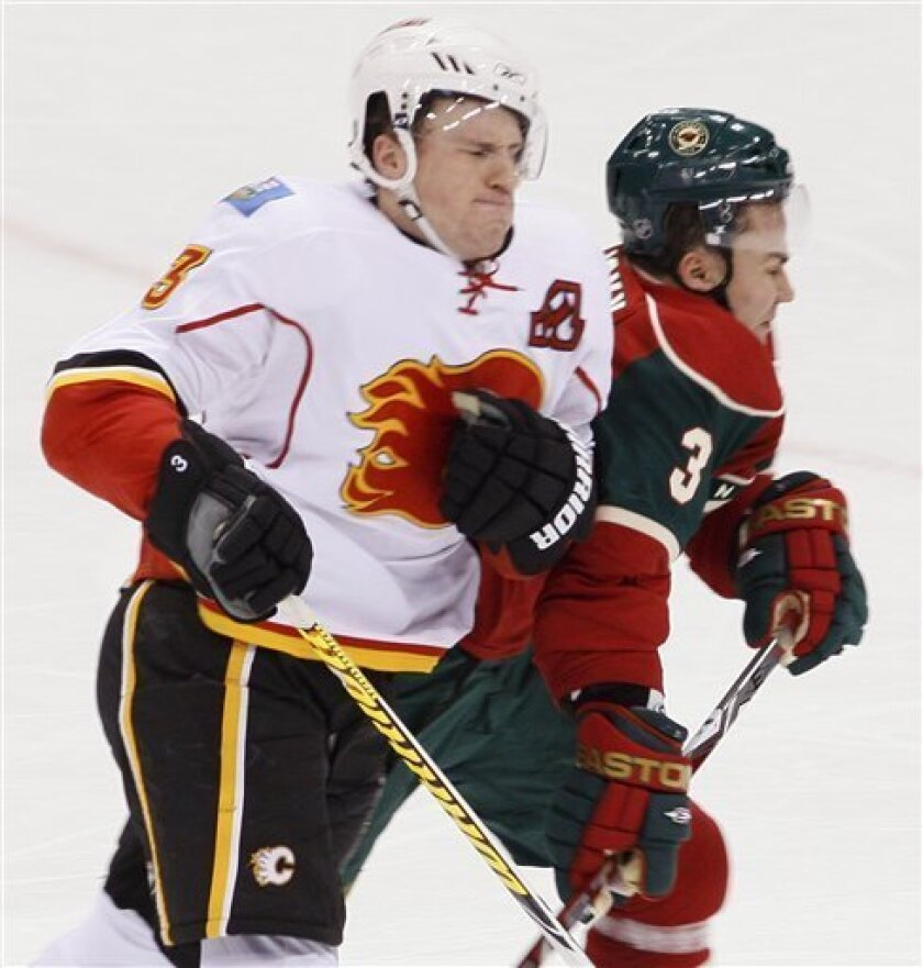 Minnesota Wild defenseman Marek Zidlicky, right, of the Czech Republic, takes a hit from Calgary Flames defenseman Dion Phaneuf, left, during the second period of an NHL hockey game in St. Paul, Minn., Wednesday, Dec. 17, 2008. (AP Photo/Ann Heisenfelt)