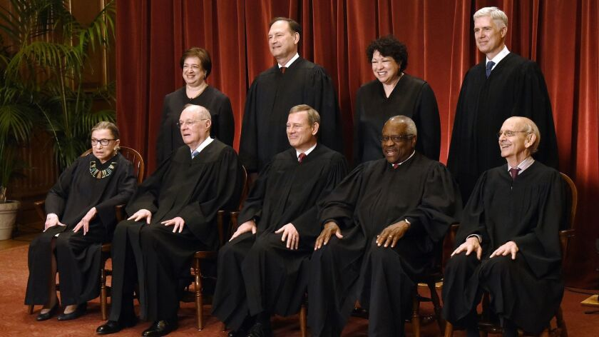 Members of the U.S. Supreme Court pose for a group photograph at the Supreme Court building on June 1, 2017.