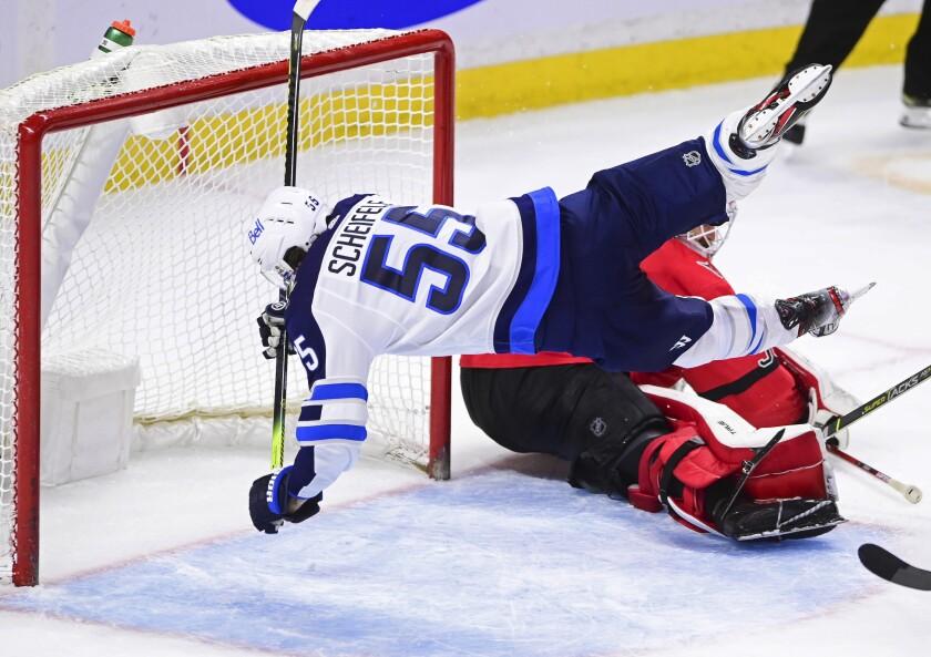 Winnipeg Jets' Mark Scheifele (55) trips over Ottawa Senators goalie Matt Murray (30) during the third period of an NHL hockey game Wednesday, April 14, 2021, in Ottawa, Ontario. (Sean Kilpatrick/The Canadian Press via AP)