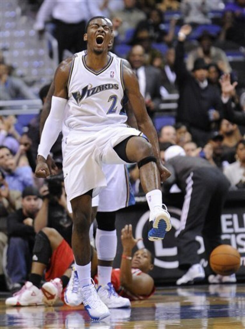 Washington Wizards' John Wall (2) reacts after his dunk during the first half of an NBA basketball game against the Houston Rockets, Wednesday, Nov. 10, 2010, in Washington. (AP Photo/Nick Wass)