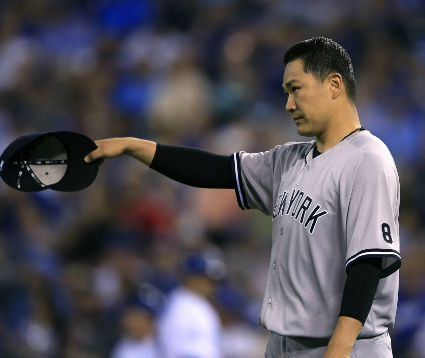 New York Yankees starting pitcher Masahiro Tanaka tips his hat to left fielder Brett Gardner after a big catch during the fifth inning of a baseball game against the Kansas City Royals at Kauffman Stadium in Kansas City, Mo., Tuesday, Aug. 30, 2016. (AP Photo/Orlin Wagner)