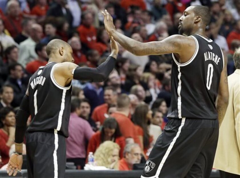 Brooklyn Nets forward Andray Blatche, right, celebrates with C.J. Watson during the second half in Game 6 of their first-round NBA basketball playoff series against the Chicago Bulls in Chicago, Thursday, May 2, 2013. The Nets won 95-92. (AP Photo/Nam Y. Huh)