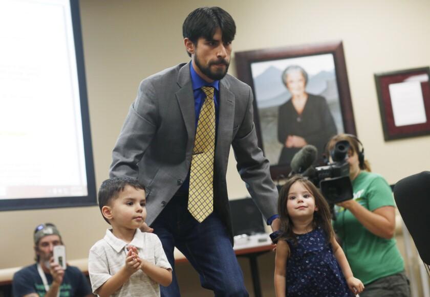El fotógrafo de combate de la Fuerza Aérea de Estados Unidos Steve Otero (centro) lleva a sus hijos a ocupar su sitio antes de la audiencia en la que expresó su apoyo a la adición del Síndrome de Estrés Postraumático a la lista de males para los que se puede recetar marihuana como tratamiento el miércoles 15 de julio de 2015 ein Denver. (Foto AP/David Zalubowski)