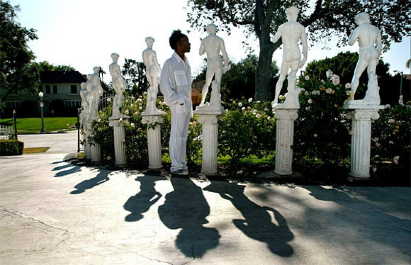 Miniature statues of Michelangelo's David curve along the front lawn of Norwood Young's home.