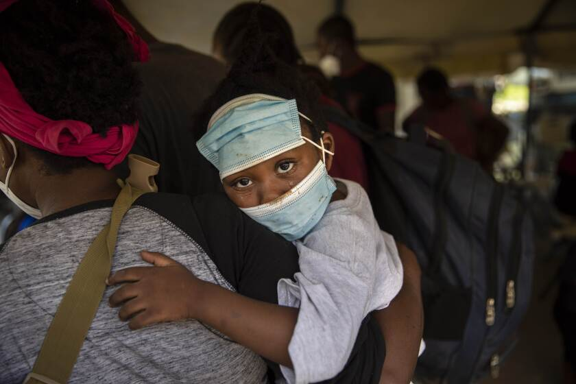 A little girl with teary eyes holds is carried by a woman who was deported from the U.S. border with Mexico at Toussaint Louverture International Airport in Port-au-Prince, Haiti, Monday, Sept. 20, 2021. The U.S. is flying Haitians camped in a Texas border town back to their homeland. (AP Photo/Joseph Odelyn)