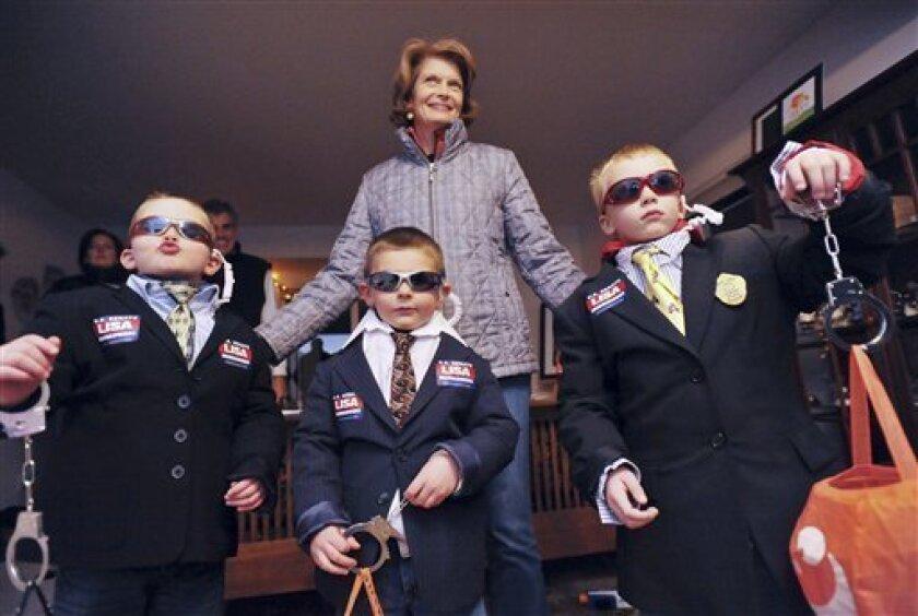 "Senator Lisa Murkowski (R-Alaska), center, poses with her Halloween ""security guards,"" from left, nephew Tate Hart, 6, Luka Hart, 4, and Jack Schroeder 6, Sunday, Oct. 31, 2010 in Anchorage, Alaska. (AP Photo / Michael Dinneen)"