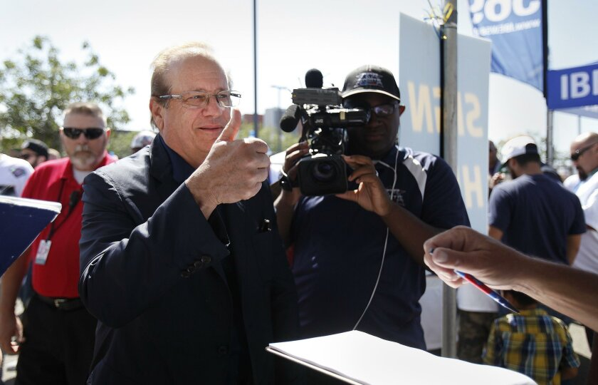 "In this April 23 file photo, Chargers owner Dean Spanos gives the ""thumbs up"" after signing the Stadium Initiative ballot petition before the start of a signature-gathering rally."