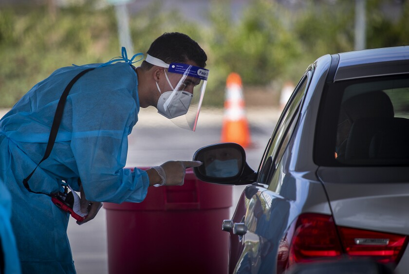 A healthcare worker talks with a motorist at the drive-through COVID-19 testing site in Costa Mesa.