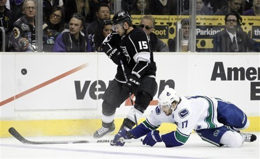 Los Angeles Kings center Brad Richardson, left, battles Vancouver Canucks center Ryan Kesler for the puck during the first period in Game 6 of a first-round NHL hockey Western Conference playoff series in Los Angeles, Sunday, April 25, 2010. (AP Photo/Chris Carlson)