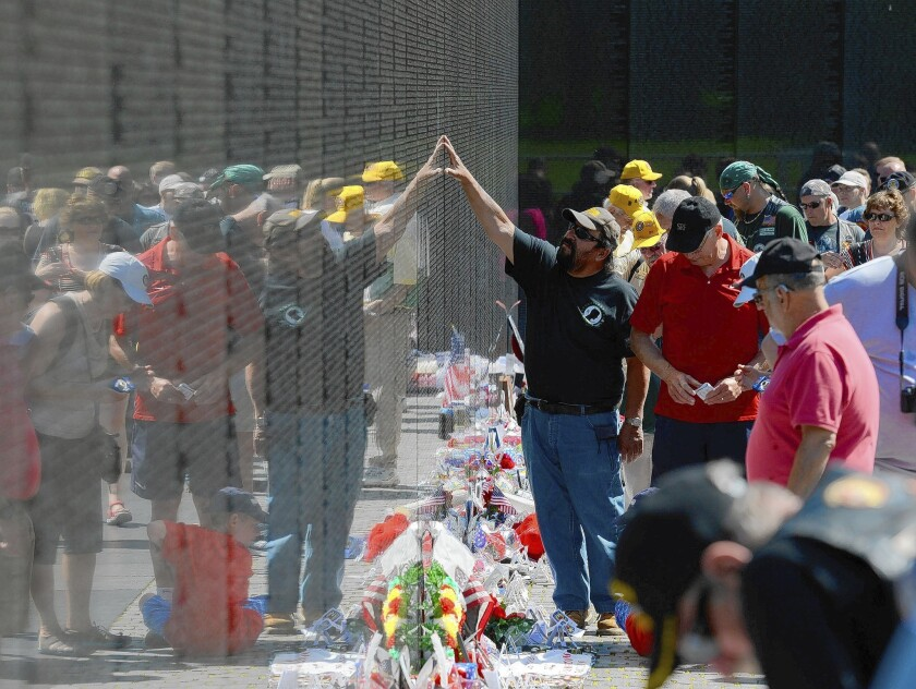 Visitors to the Vietnam Veterans Memorial in Washington. The wall bears the names of 58,300 men and women killed or missing in action.