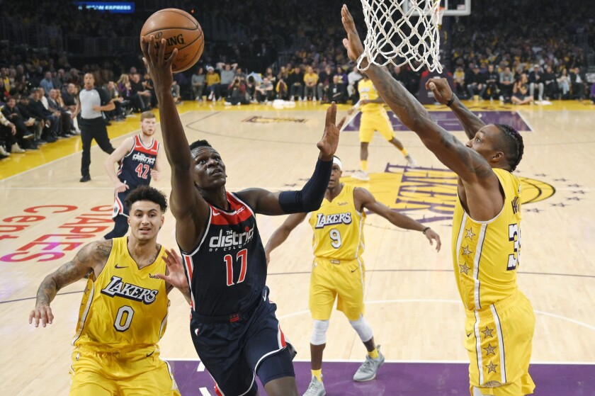 Kyle Kuzma, left, trails on the play as the Wizards' Isaac Bonga goes up for a shot Nov. 29, 2019.