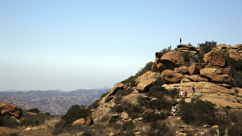 Photographed from the junction of the Hummingbird trail and the Rocky Peak trail, hikers climb the rocks off of the Hummingbird trail.