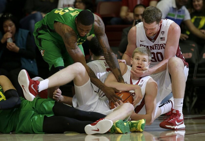 Stanford's Michael Humphrey, center, is congratulated by Grant Verhoeven (30) after grabbing the ball and calling a timeout under Oregon's Elgin Cook (23) during the second half of an NCAA college basketball game in Stanford, Calif., Saturday, Feb. 13, 2016. Stanford won 76-72. (AP Photo/Jeff Chiu)
