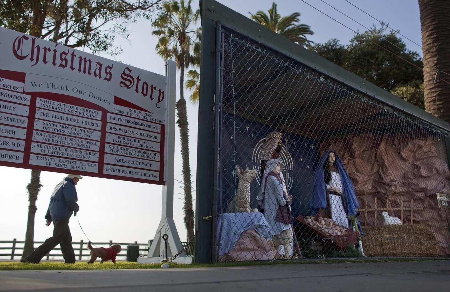 A woman walks her dog along the dirt path behind the Nativity scene at Pacific Palisades Park along Ocean Avenue.
