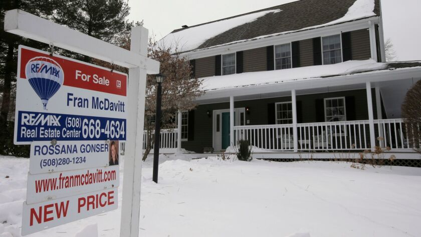 A for sale sign hangs in front of a home in Walpole, Mass., in January.