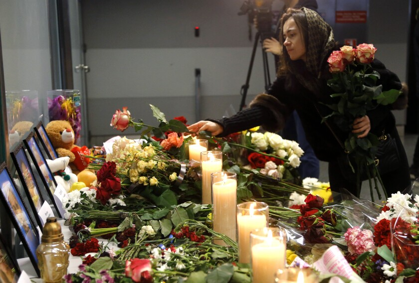 A woman lays flowers at a memorial of the flight crew members of the Ukrainian 737-800 plane that crashed on the outskirts of Tehran.