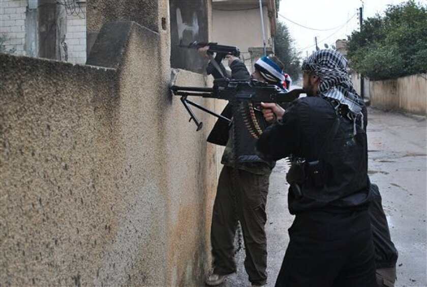 Syrian rebels take their position behind a wall as they fire their guns during a battle with the Syrian government forces, at Rastan area in Homs province, central Syria, on Tuesday Jan. 31, 2012. Syrian troops crushed pockets of rebel soldiers Tuesday on the outskirts of Damascus, fueling some of the bloodiest fighting of the 10-month-old uprising, as Western diplomats tried to overcome Russia's rejection of a draft U.N. resolution demanding President Bashar Assad halt the violence and yield power. (AP Photo)
