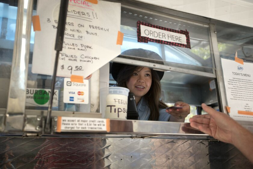 In this photo taken, July 10, 2015, food truck Peaches' Smokehouse & Southern Kitchen co-owner Diana Lamon hands a credit card back to a customer after taking an order in Burbank, Calif. The health care law, minimum wage increases and paid sick leave laws in some states and cities are increasing costs for business owners like Lamon. (AP Photo/Jae C. Hong)