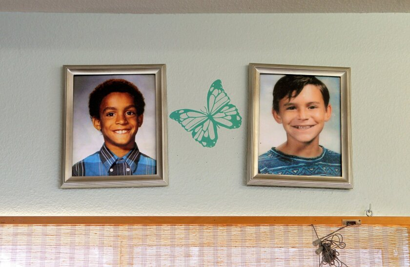 Jonathan Sellers and Charlie Keever's photos hang on the wall of Milena (Sellers) Phillips thrift shop in Fallbrook