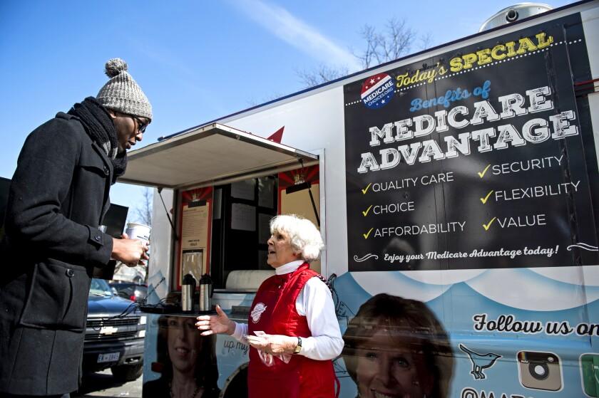 Two people stand in front of a trailer with a sign about Medicare Advantage plans.