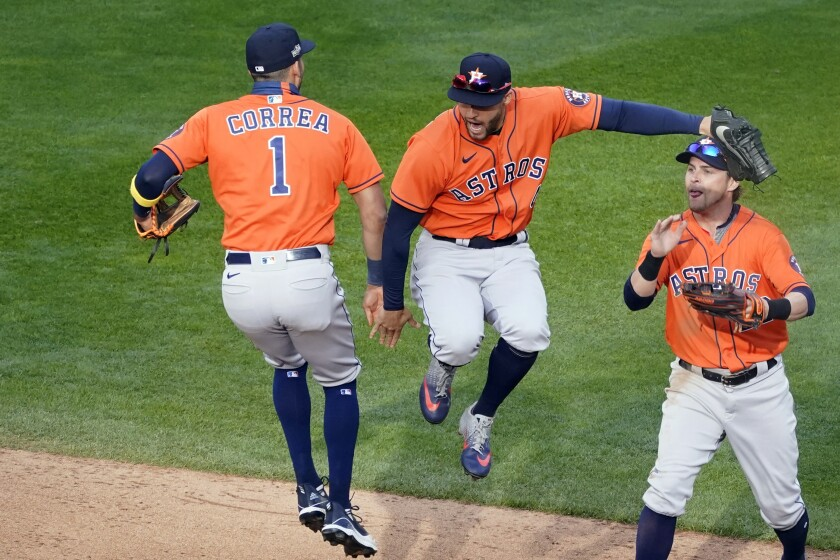 Houston's Carlos Correa, left, and George Springer jump in celebration next to Josh Reddick