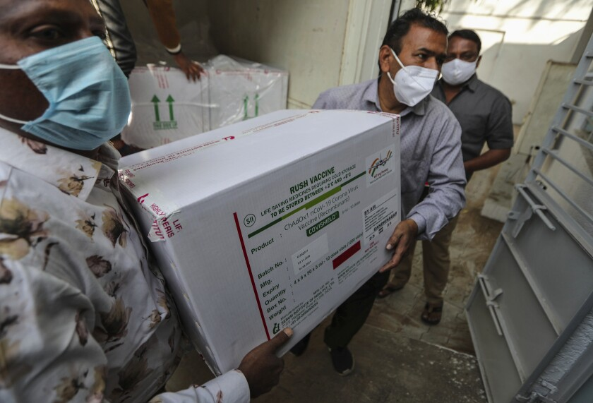 """People wearing masks carry a large white cardboard box with a label that reads """"rush vaccine"""""""