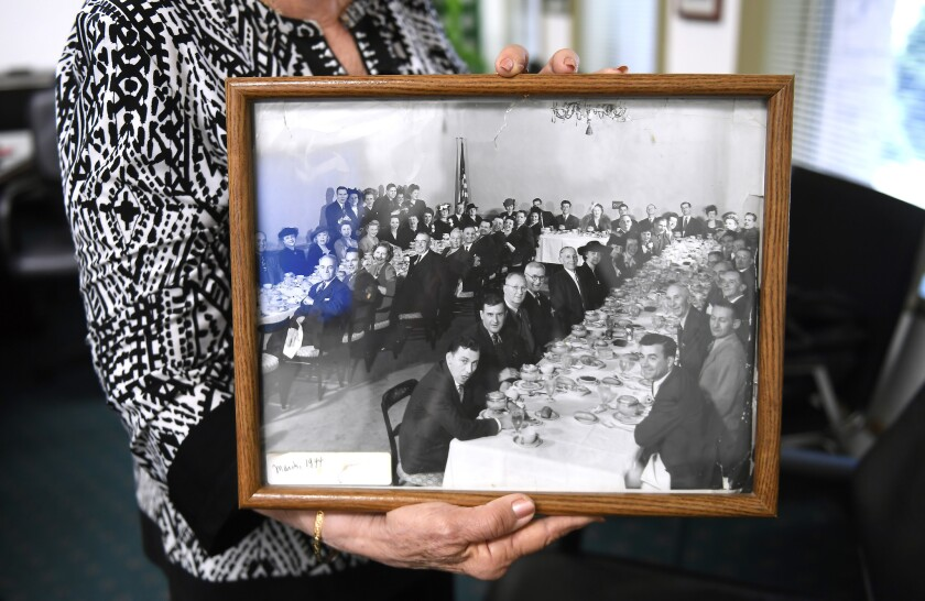 Raquel Bensimon, who led Dearden's for nearly two decades, holds a photograph of employees taken in