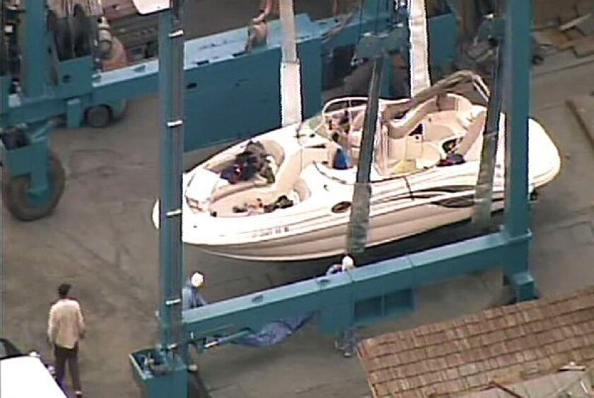 The pleasure boat struck by a Coast Guard vessel in a fatal accident Sunday evening is visible in drydock at the Shelter Island Boat Yard in this image taken from aerial video. (KGTV Channel 10)