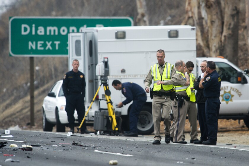 Officials investigate the scene of a three-vehicle crash where six people were killed on the westbound 60 Freeway in Diamond Bar.