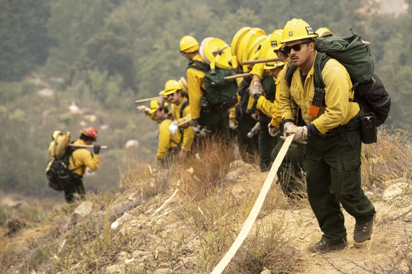 Members of the Mormon Hot Shots from Arizona lay hose line down rugged terrain off Highway 39 near Crystal Lake in front of the Bobcat Fire, which has burned more than 23,000 acres, Thursday, Sept. 10, 2020. (David Crane/The Orange County Register via AP)
