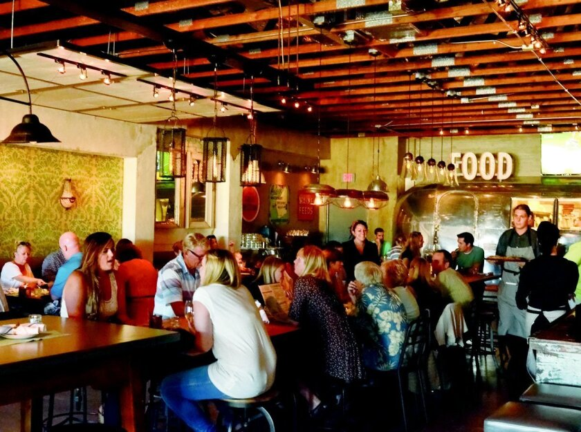 Patrons gather around a communal table in the dining room at OB Warehouse in Ocean Beach.