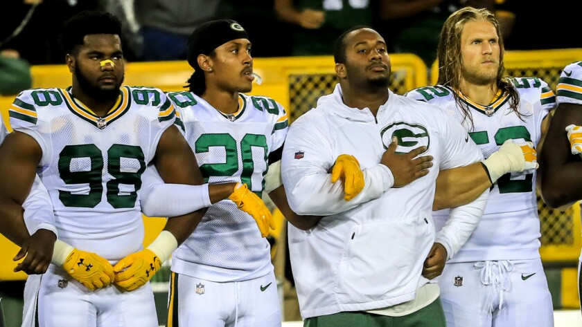 Packers players lock arms during the playing of the national anthem before Thursday night's game against the Bears.