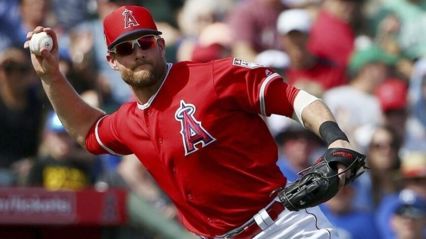 Los Angeles Angels third baseman Zack Cozart, right, readies to throw the ball to first base to get