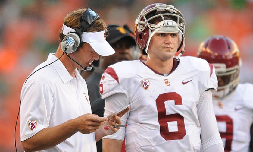 Lane Kiffin goes over plays with quarterback Cody Kessler in the season opener at Hawaii.