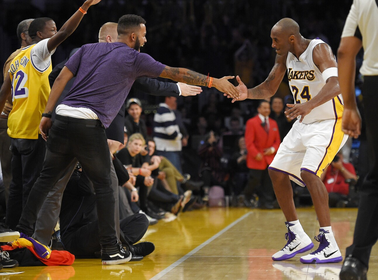 Los Angeles Lakers forward Kobe Bryant, right, celebrates with Anthony Sadler, front left and Spencer Stone, obscured, after hitting a 3-point shot during the second half of an NBA basketball game against the Detroit Pistons, Sunday, Nov. 15, 2015, in Los Angeles. Sadler, and Stone are two of three Americans who helped stop a terrorist attack on a train in France in August. The Lakers won 97-85. (AP Photo/Mark J. Terrill)