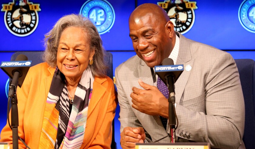Rachel Robinson, widow of Jackie Robinson, and Dodgers co-owner Magic Johnson share a laugh before a news conference to announce that a statue of her late husband will be erected at Dodger Stadium.