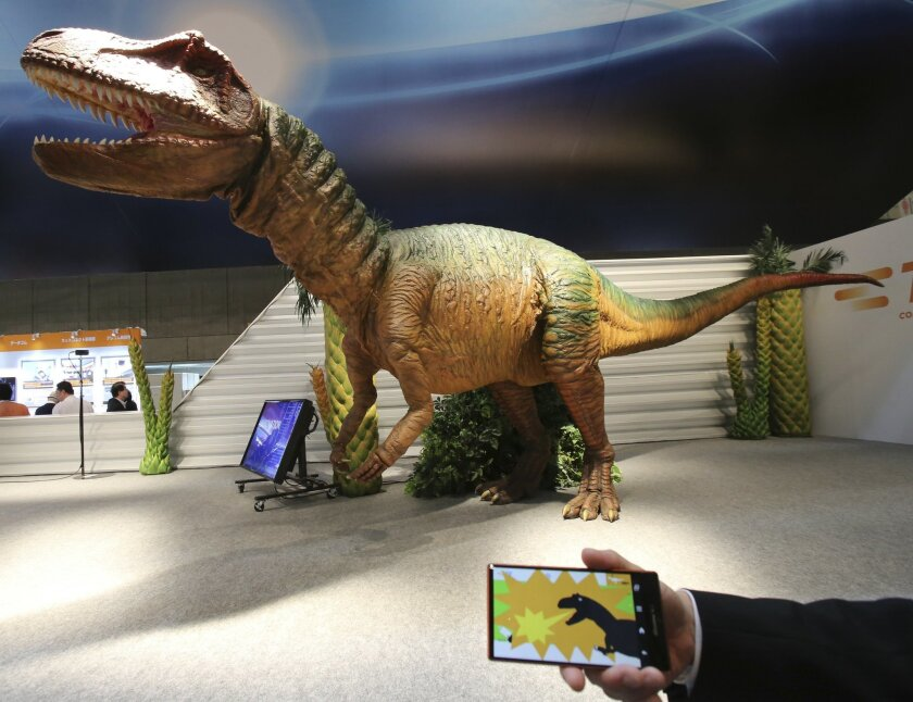 """A TE Connectivity Japan staff member demonstrates how to control remotely its dinosaur robot """"TE Saurus"""" by a smart phone during the annual CEATEC Japan advanced technologies show in Chiba, east of Tokyo Tuesday, Oct. 7, 2014. With a Sharp Aquos ZETA mobile phone model, users can make the 6.5-meter (21 feet, 4 inches) long, 2.1-meter (6 feet, 11 inches) tall dinosaur robot to walk forward and backward, jump, move its head, hands and legs up and down, left and right, open and close its mouth by touching the screen panel and make it bark by shaking the handheld. (AP Photo/Koji Sasahara)"""