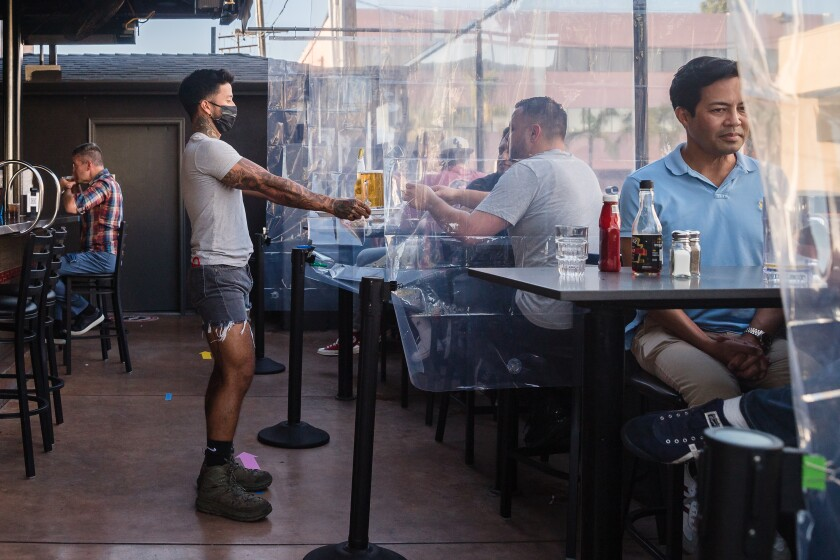 Customers sit at tables divided with clear plastic shower curtains at Urban MO's Bar & Grill on July 2, 2020 in Hillcrest