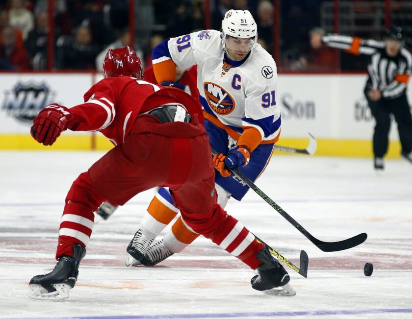 New York Islanders' John Tavares (91) moves the puck past Carolina Hurricanes' Jaccob Slavin (74) during the first period of an NHL hockey game, Saturday, Feb. 13, 2016, in Raleigh, N.C. (AP Photo/Karl B DeBlaker)