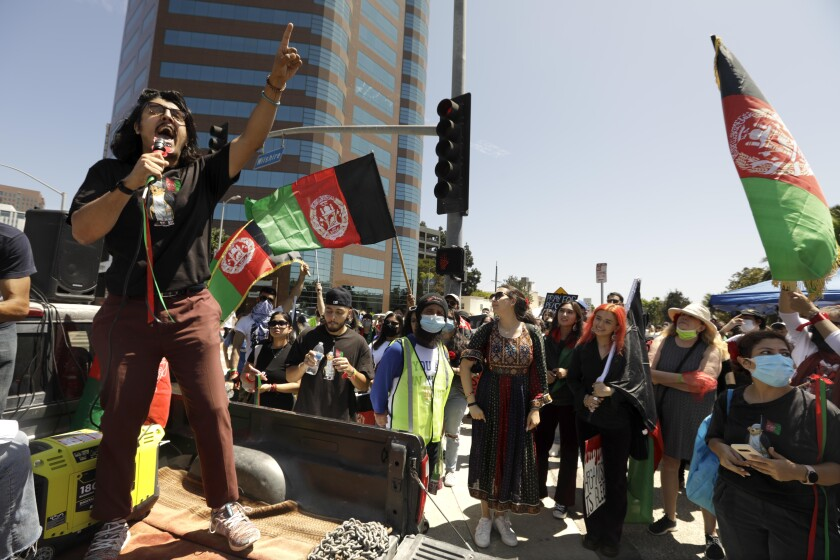 Afghan American activist Arash Azizzada, left, speaking to a crowd in Los Angeles.