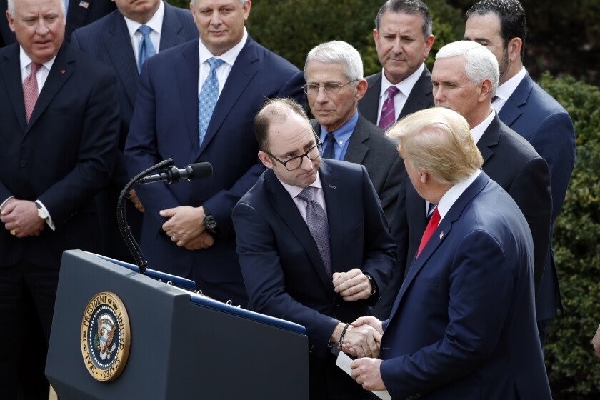 President Donald Trump shakes hands Richard Ashworth, president of Walgreens, during a news conference about the coronavirus in the Rose Garden at the White House, Friday, March 13, 2020, in Washington. (AP Photo/Alex Brandon)