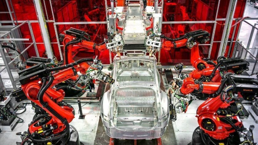 Robots dominate an assembly line at the Tesla car factory in Fremont, Calif.
