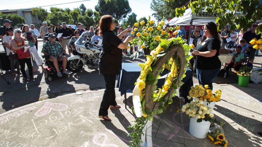Luisa Lococo, center, whose mother died in the crash, places flowers in a vase for each name of a victim read out loud during a memorial ceremony marking the anniversary of the PSA Flight 182 crash in 1978 in North Park on Sunday.